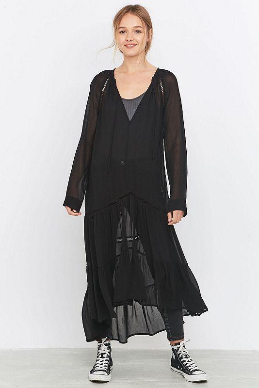 Dieses transparente, schwarze Kleid mit tiefer Taille vom Urban Outfitters Exclusive Label Pins & Needles macht dich zu einer kleinen Hexe. Das Modell aus transparentem, schwarzem Chiffon verfügt über eine tief sitzende Taille, gehäkelte Ziernähte, einen geschnürten V-Ausschnitt und extralange Ärmel. Das Design wird durch den gestuften, flatternden Saum abgerundet.   **WISSENSWERTES:**  - Mischgewebe  - Maschinenwäsche   **GRÖSSE UND PASSFORM:**  - Das Model trägt Größe: Small  - Größe de...