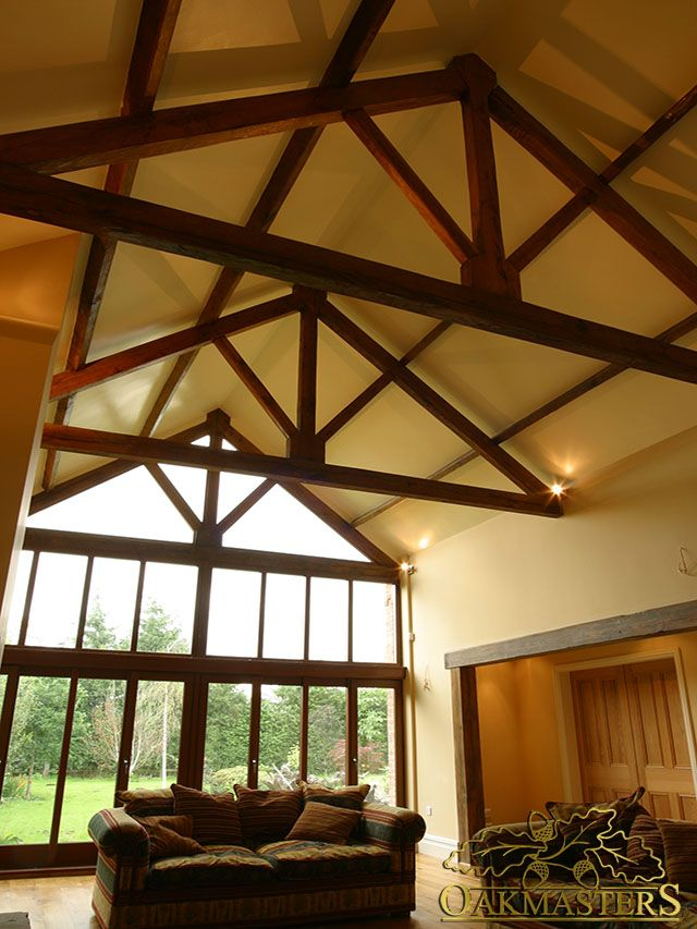 Interior of an oak framed garden room with a row of king post oak trusses.