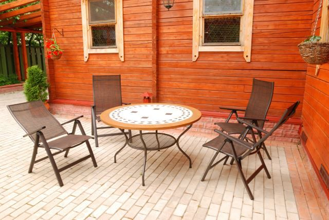 This is the type of scene you'd probably see out in the wilderness in a cabin or lodge. The natural wood in the background indicates that this is probably a heavily wooded area and requires that type of patio furniture to match. The brick is a classy way to get rid of just plain dirt flooring and gives you room to add some interesting elements to match the scenery. The chairs give this scene a more modern look that would no doubt make any passerby want to sit and take in the scenery for a…