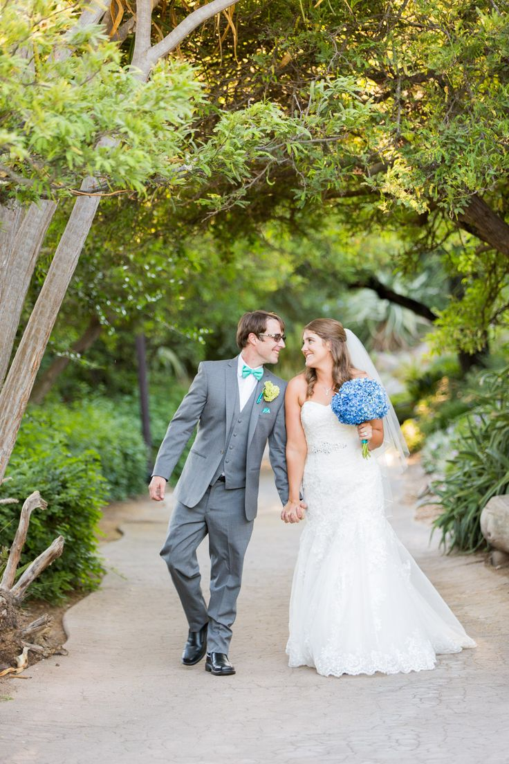 Groom and bride with blue hydrangea bouquet walking around the San Diego zoo safari park for their wedding, San Diego Zoo Safari Park Wedding