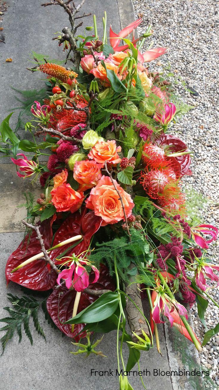 Een rouwstuk met tropische bloemen.