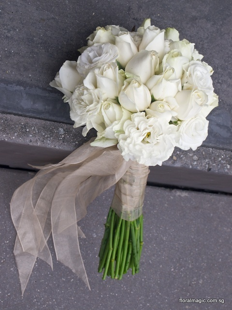 you won't go wrong with pure white eustoma and roses for a bridal bouquet. add champagne ribbons for a softer feel. by www.floralmagic.com.sg