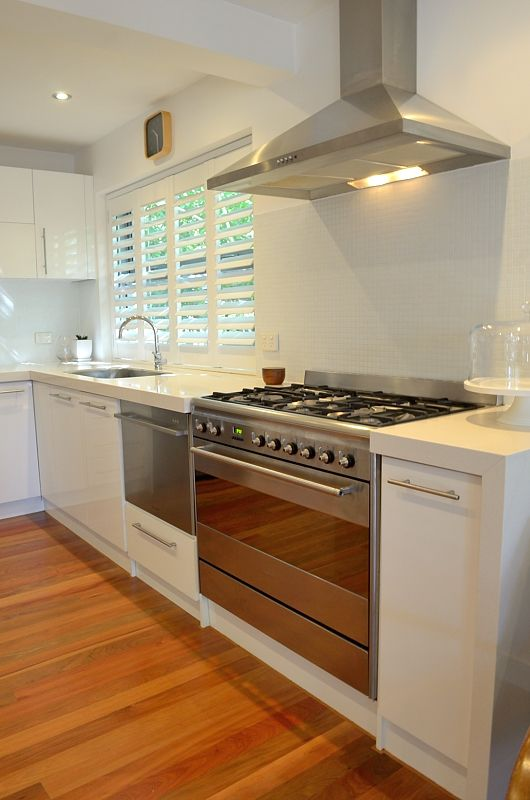 Open plan kitchen with white plantation shutters, thick stone benchtops, hard-wearing Blackbutt timber floors opening out to sunny courtyard gardens- a great place for a BBQ lunch after a surf.