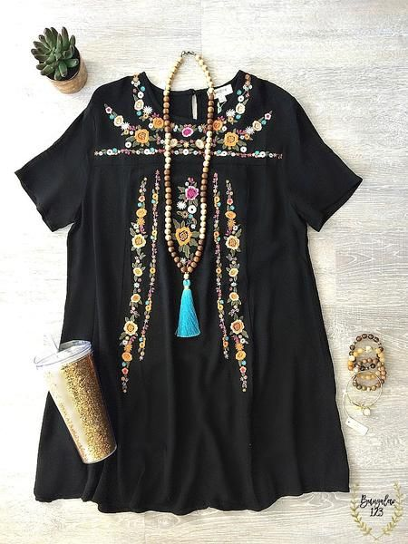 Festive little black dress featuring floral embroidery on front. A-line pullover style with single button at nape of neck. Shown with the Turquoise Silk Tassel Necklace and Acrylic Tumbler in Gold. Ra