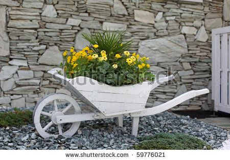 pictures of flower beds in front of house | Flower bed pushcart in front of a house - stock photo