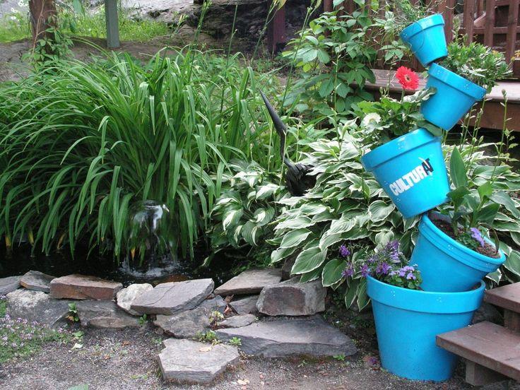 Sylvie Malenfant participe au décor  Je cherchais un projet qui utilise seulement des matériaux recyclés. J'ai donc utilisé de vieux pots de terre cuite que j'ai peinturés aux couleurs de CULTURAT et j'y ai planté de jolies fleurs. Étant situées à l'ombre, peu de fleurs s'épanouissent autour du jardin d'eau, le bleu amène donc une touche de vie étonnante dans ce petit coin de paradis !!!