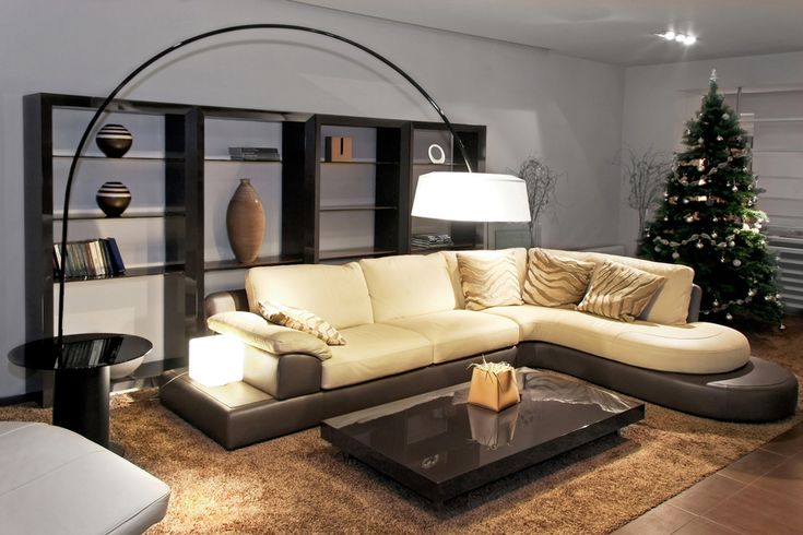 Living room with low black platform coffee table, plush beige sofa with brown base and black bookshelves