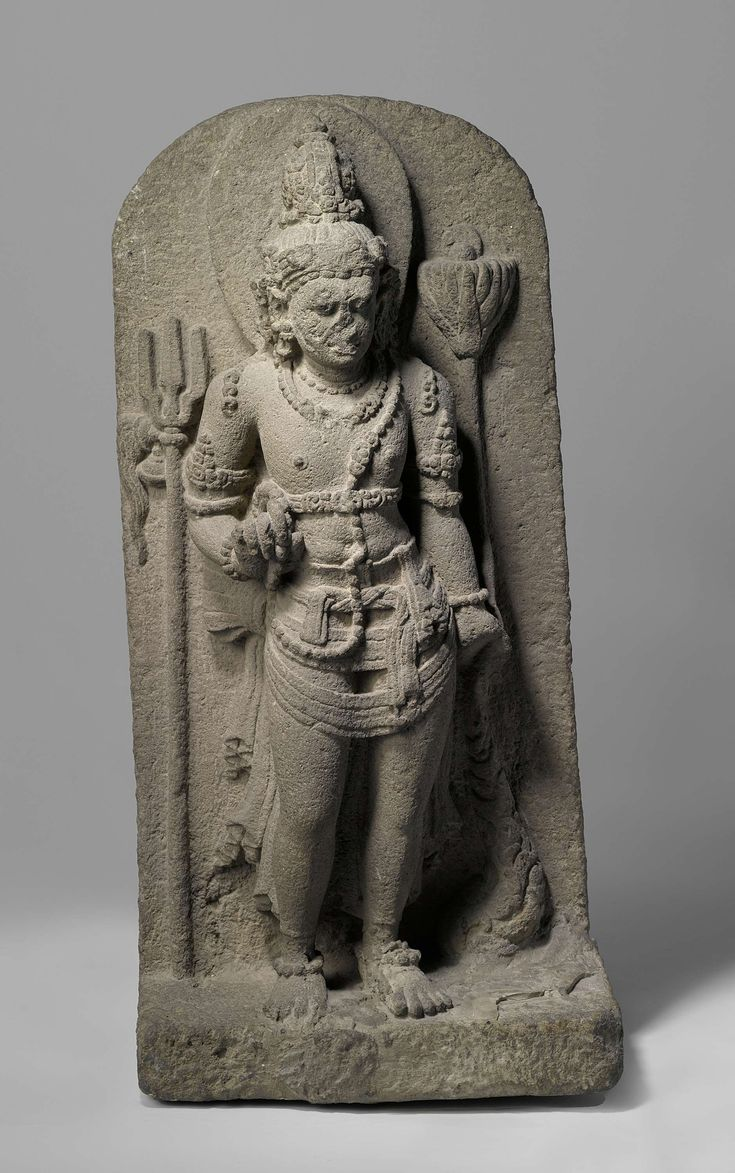 Nandishvara, Anonymous, 800 - 900.Midden-Java.Nandishvara is one of the two guards at the entrance to temples of the Hindu god Shiva. He has the appearance of an elegant young man and stands on Shiva's right side. In one hand he holds a circle of prayer beads, in the other a floating lotus flower. The trident is the weapon of Shiva.
