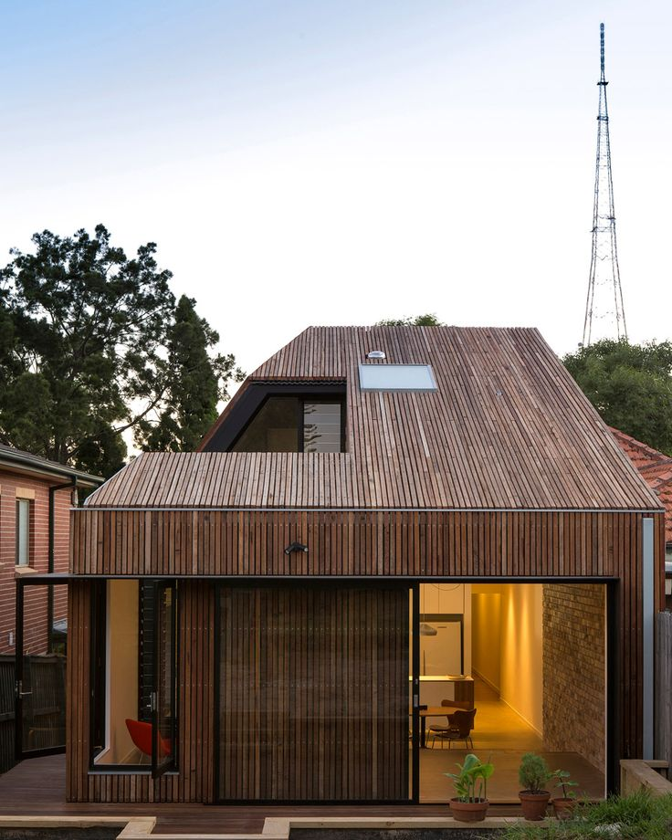 A hole in the roof of this timber-clad house extension in Sydney reveals the location of a secluded courtyard