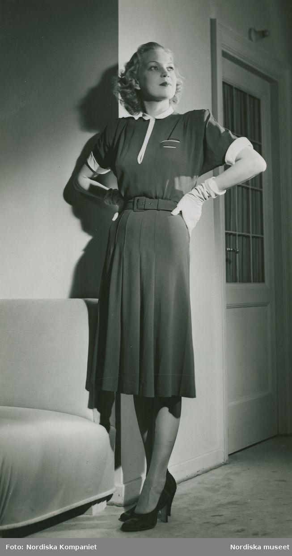1941. Modell i kortärmad klänning med skärp, handskar och pumps, framför en dörr och soffa. Modell: Margit Langlet. Foto: Erik Holmén för Nordiska Kompaniet