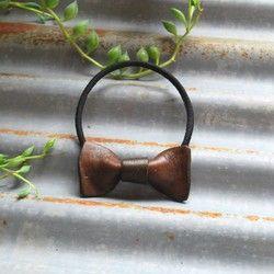 手染めで染色したヌメ革のリボン型ヘアゴム。忙しい朝もサッと結ぶだけでオシャレに大変身!小さめのリボンなので、どんなコーディネートにも合わせやすいですよ。ゴムが伸びてしまったら、お手持ちのヘアゴムに取り替えOK♪●material:牛ヌメ革●size:約タテ25mm×ヨコ45mm●ヘアゴムカラー:ブラウン【Leather】植物タンニンなめしのヌメ革を使用していますので使うほどに色に深みと艶が増し、ユーザーオリジナルのエイジングをお楽しみ頂けます。【concept】Roy G Biv(ロイジービブ)とは虹色を覚えるコトバで7色の頭文字が並べられています植物タンニン鞣しのヌメ革を使った革小物、Leather accessoryは染色、縫製、仕立てまですべてハンドメイドシンプルなカタチ+「ひと工夫」そして手染めによる革の色彩をお楽しみください◇facebook https://facebook.com/roygbiv2009◇instagram @roygbiv_yasuko  https://www.instagram.com&#x2F...