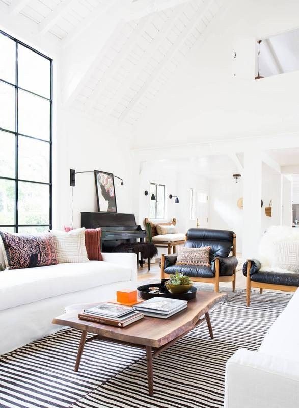 Bright bohemian inspired living space with high ceilings, large glass windows, a white sofa, matching leather armchairs, and a stripped rug