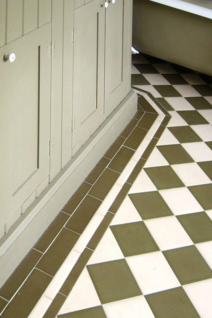 Badrum med inbyggt badkar. Cremefärgat kakel av typen half tile satt i tegelförband med mörkgrå fog.