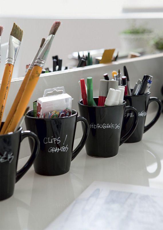 Para acondicionar pincéis, canetas e clipes, Ana Luiza recorre a canecas identificadas. Foram compradas peças de cerâmica esmaltada todas iguais. O nome do que vai dentro é escrito com caneta hidrográfica.