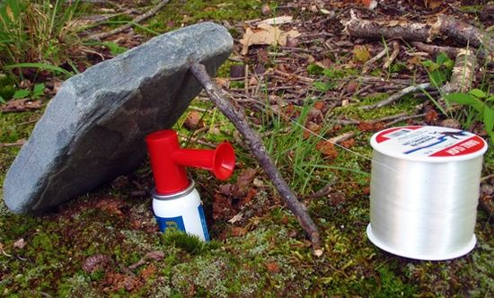 Perimeter alarm for a camp with an air horn, fishing line, a heavy rock, and a stick. Hmm, maybe this could stop the heron from UNstocking the fish pond!