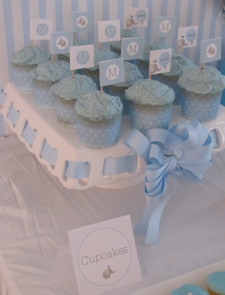 Blue cupcakes with little elephant flag toppers.