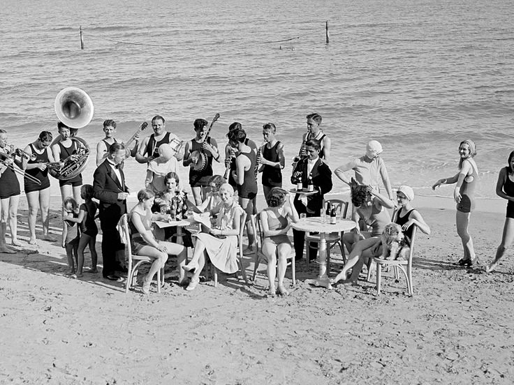 """""""A festive gathering under the azure skies at Miami Beach FL. Jazzy tunes rendered by a band encourages some of the damsels to cut a few terpsichorean figures on the sand. Strictly informal attire is the rule of etiquette at these frolics with bathing suits, the correct mode."""""""