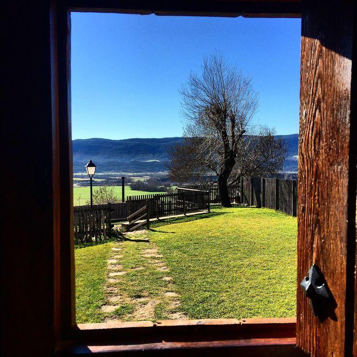 Ventanuco de puerta vieja de madera hacia el jardín