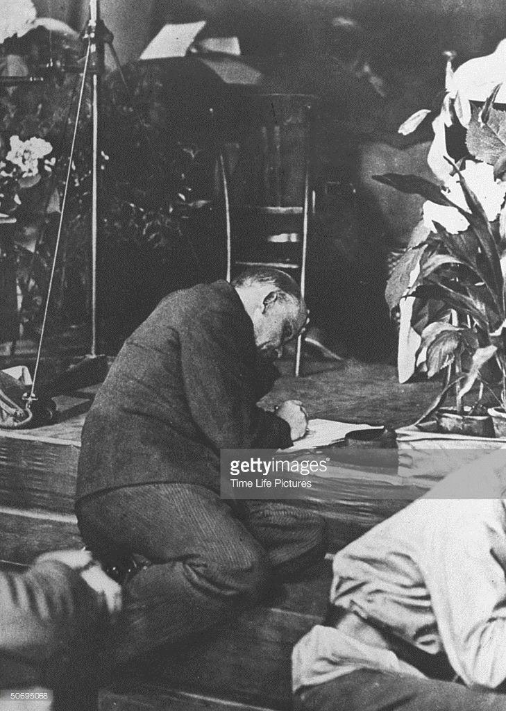 Russian Communist leader Vladimir Lenin (1870 - 1924) sitting on steps to podium…