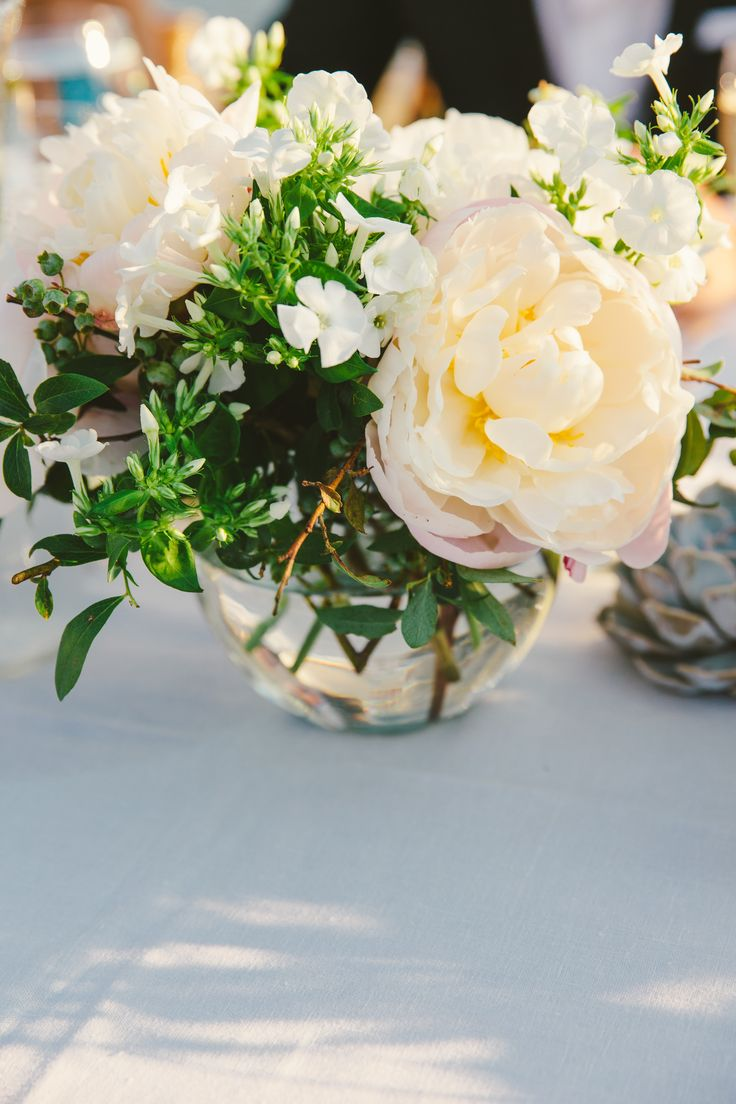 Flower table decorations - Arrangements Of Peonies And Stephanotises In A Variety Of Glass Vases Created A Romantic Eclectic Dinner Table