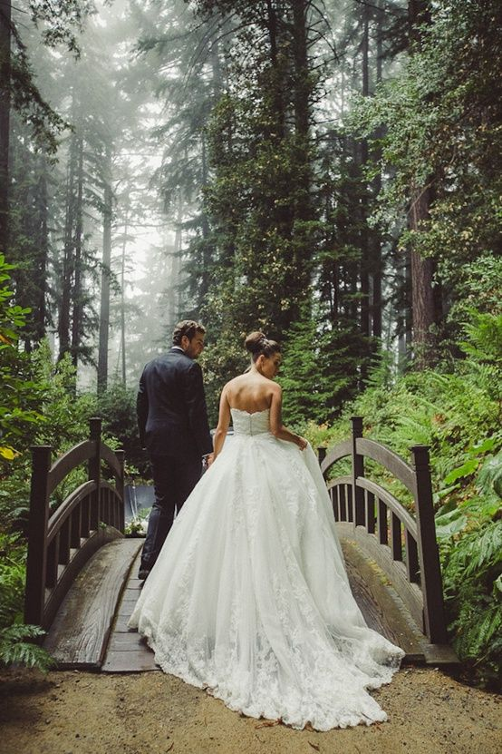romantic and fairytale wedding gown walking in an enchanted forest