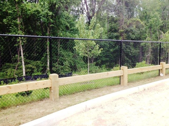Commercial wood guard rail and black chain link fencing