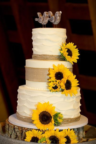 Sunflowers, twine, burlap, and wooden accents are hallmarks of a rustic wedding, and this cake showcases them all to stunning effect.