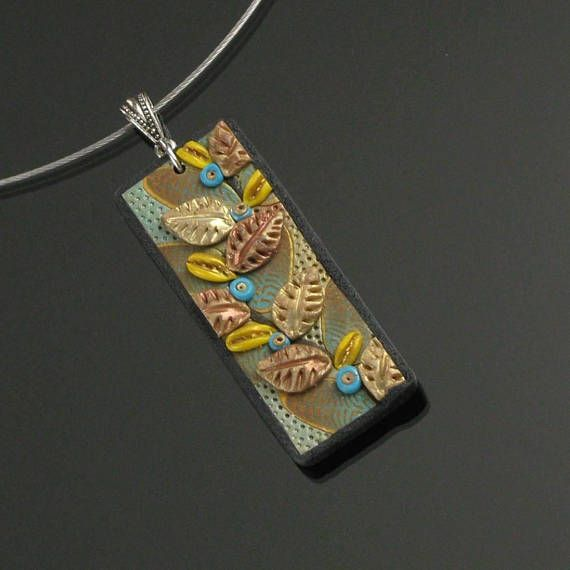 Earthy gold & coppery clay leaves cascade along a fantastical vine that bears aqua berries (...anything is possible in the world of polymer clay!). The vine motif rests on a gold and turquoise clay cane work leaf background with a black clay border trim. The pendant backing is textured