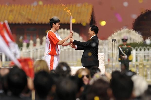 Chinese President Hu Jintao (R) hands the Olympic torch to track star Liu Xiang ahead of the 2008 Summer Olympics in Beijing, China. (Getty ...