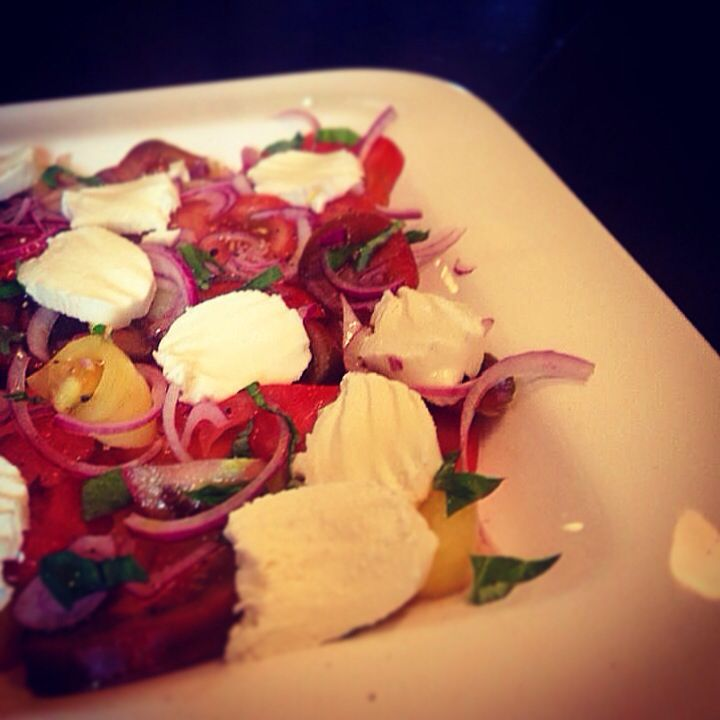 Heritage tomato and mozzarella salad with red onion and basil.