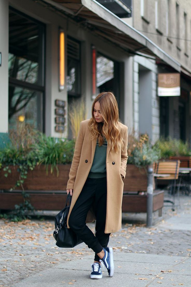 Elena Pellicano looks cute and casual in a camel overcoat and black drop crotch trousers. Coat: Promod, Sweater: Isabel Marant, Sneakers: Vans.