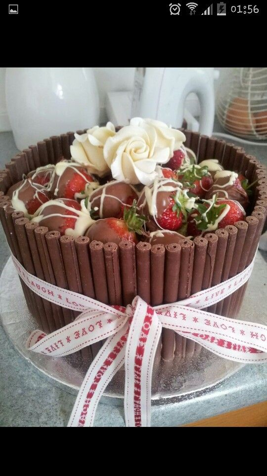 Mothers birthday cake! Chocolate fudge cake with chocolate and vanilla butter cream covered with milk choc cigarellos. East of India ribbon. Choc covered strawberries and 3 chocolate flowers on top!