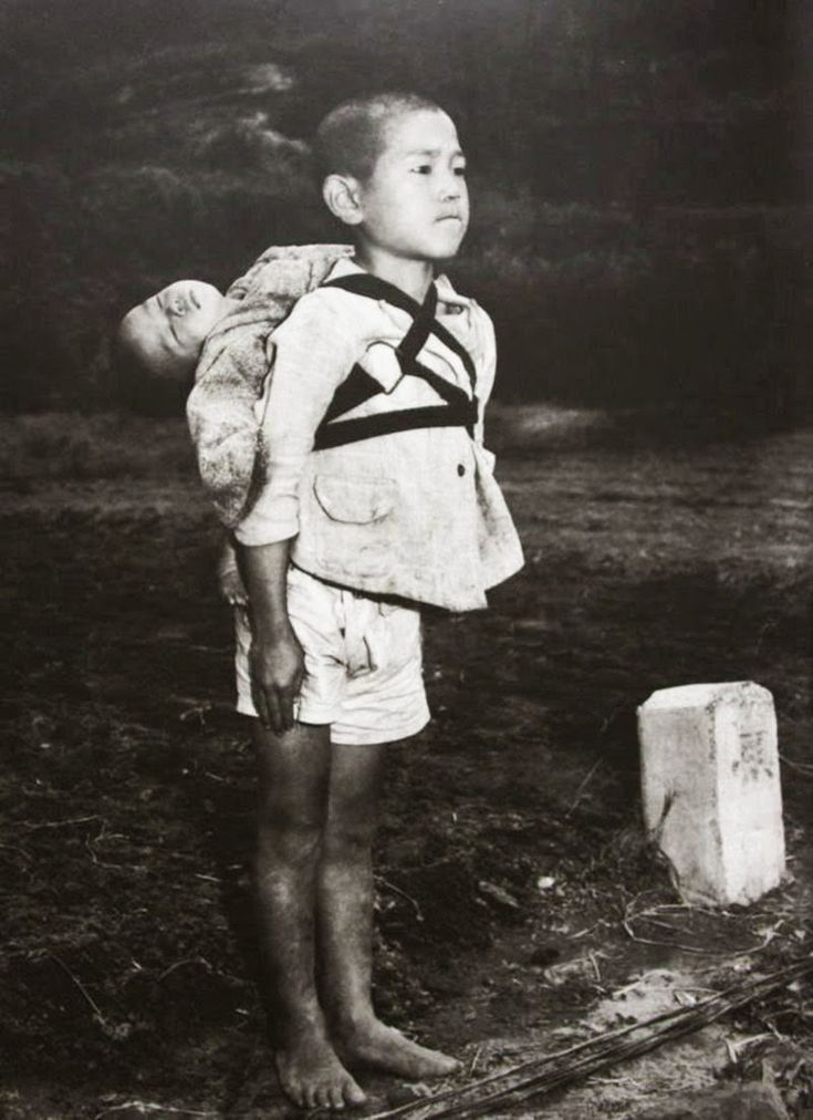 A Japanese boy standing at attention after having brought his dead younger brother to a cremation pyre, 1945
