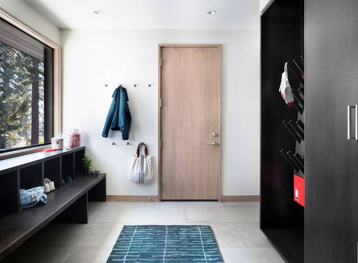 The large window in this modern mudroom lets in plenty of light that's reflected off the white walls. Tiny wall hooks create an area to hang your jacket, while a dark wood drying rack sits on one wall, and under the window a bench with open storage cubbies creates a spot for putting on your shoes.