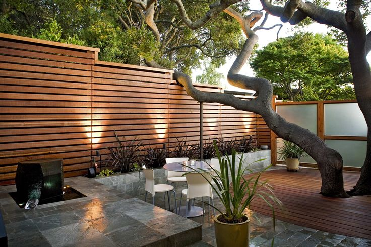 Charming Horizontal Slat Fence Creates Landscape Boundaries: Horizontal Slat Fence With Exterior Lighting And Water Fountain Also Flagstone And Patio Furniture With Retaining Wall Plus Wood Decks