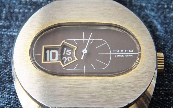 Buler Jump Hour digtaal polshorloge - Mannenhorloge - Rond de jaren '70  Deze veiling is voor Buler Digital Mechanical (Jump Hour) Horloge van 1970 in uitstekende conditie.Alle onderdelen zijn origineel zoals op de foto's.Fabrikant: BulerModel: Digitale mechanische (sprong uur) mannen horloge - Circa 1970sMovement: Mechanical - Wind-up - ShockresistantMateriaal: Metalen behuizing en staal terug.De grootte van het geval: Diameter: 38mm (zonder de kroon) en lengte: 33mmTotale lengte: ca. 22cm…