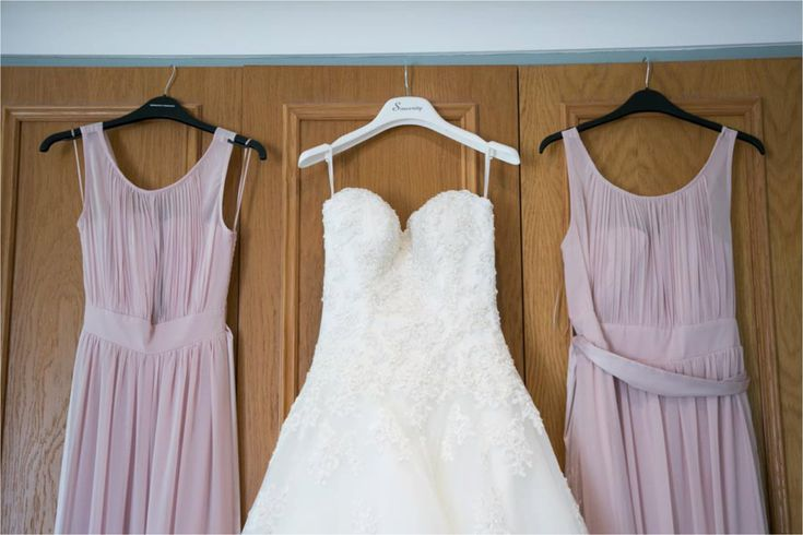 dusky pink bridesmaid dressed hanging up with wedding dress,stole by Nayland wedding photography