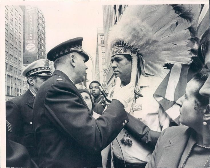 Policeman stopping Chippewa William Wiggens, VP of the Chicago Indian Village, from entering the Columbus Day parade at Madison and State Streets. Dated October 12, 1970.