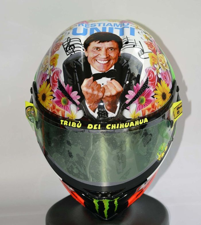 """Valentino Rossi 'Lets Stick Together' Helmet (Mugello 2012): For the 2012 Italian MotoGP at Mugello Valentino came out with a very Italian helmet that featured Gianni Morandi, a famous Italian singer and all round cult-figure, and his catchphrase """"Restiamo uniti"""" which can be translated as """"Lets Stick Together"""" which many fans thought contained a message.  Probably one of Valentino's most flamboyant Mugello helmet designs ever."""