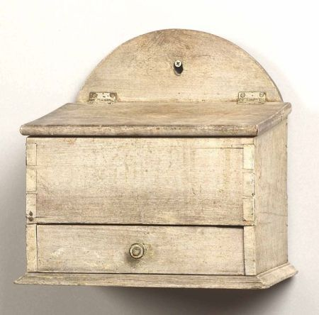 Painted Wooden Wall Candlebox, America, early 19th century, pierced arched back on rectangular dovetail constructed box with hinged slant-lid with two interior compartments, lower drawer with four compartments, old white paint, (minor cracks), ht. 11 1/8, wd. 11 1/2, dp. 7 1/4 in.  Sold for $ 1,645Wooden Wall