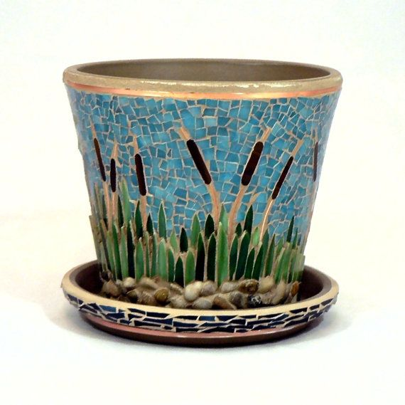 """""""Down by the Lake"""" is a unique multidimensional piece that portrays the beauty of elegant cat tails swaying in the wind and a single lone duck floating peacefully along the shore. This piece has been done with washed stone pebbles, copper wire, and stained glass."""