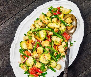Brysselkålssallad med två sorters bönor och grillad paprika, toppas med mandelrostade krutonger gjorda på surdegsbröd. Perfekt på buffébordet eller som lunch i mellandagarna. Det är pestodressingen som förgyller denna sallad tillsammans med färsk persilja.