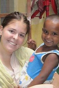 Kayla Mueller in India, holding a young child.