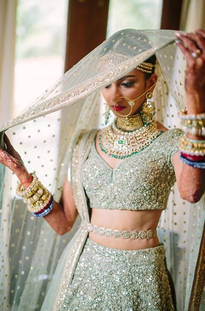 Bridal Details - Sequinned Mint Green Lehenga | WedMeGood | Mint Green Bridal Lehenga with Waist Belt, Polki and Emerald Choker Necklace, Gold Nath and Pearl and Gold Bangles #wedmegood #indianewedding #indianbride #mint #green #lehenga #bridal #sequinns