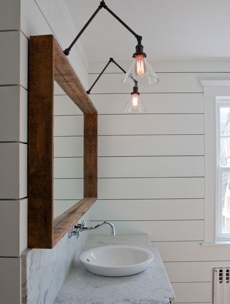 Ship lap, handsome wood mirror, and swing arm lamps. interior. bathroom. nautical. design. decor. basin.