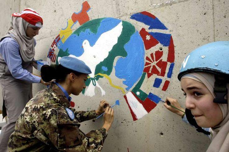 OBJETIVO 16: TORNAR A PAZ E A JUSTIÇA INSTITUIÇÕES FORTES Crianças libanesas e uma militar da força de paz italiana pintam uma parede da sede das Nações Unidas no Líbano no Dia Internacional da Paz na cidade de Naqura, sul do Líbano16 - Mahmoud Zayyat/AFP/Getty Images
