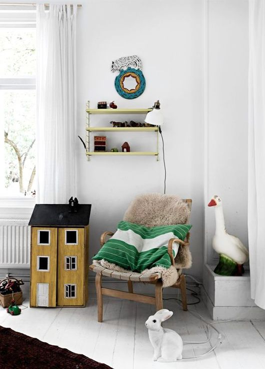Cozy nook in a children's room. We also love the painted white floors and the yellow doll house.