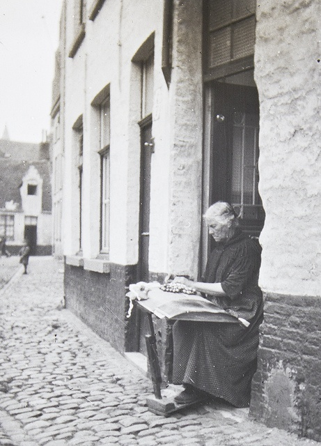 Bruges, a woman sits on the doorstep with her lace pillow, making handmade bobbin lace.