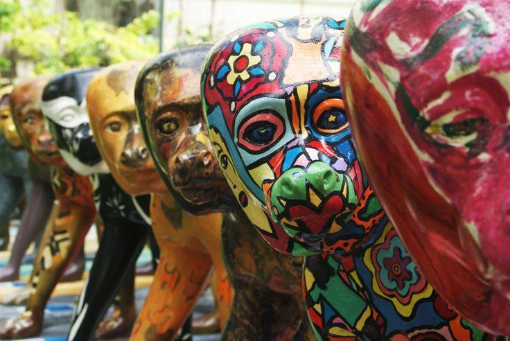 """Coloridos e de estilos variados, 26 """"cebus flavius"""" tomam o território do Palacete das Artes, em Salvador, e se espalham pelo jardim. São macacos pregos esculpidos em fibras de vidro e pintados por 27 artistas convidados. A ideia é da ONG MAC – Macaco AIDS Crianças -,  fundado pela norte-americana já radicada na Bahia, Lynn Filippucci, e inspirada na CowParade, exposição de arte pública famosa em todo o mundo."""