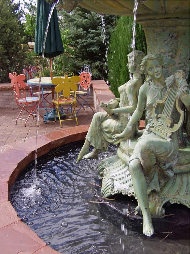 A classical European-style fountain is paired with whimsical seating in this Keith Anderson-designed landscape. From 15 Unique Water Gardens